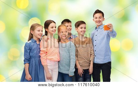 childhood, friendship, technology and people concept - happy children talking selfie by smartphone over green lights background