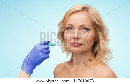 beauty, anti-aging cosmetic surgery concept - woman face and beautician hand in glove with syringe making injection to lips over blue background