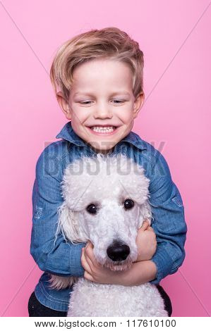 Beautiful boy with Royal Standard Poodle. Studio portrait over pink background.