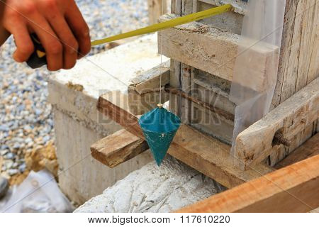 Labor Man Using A Plumb Bob For Check .