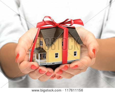 Real Estate Concept - Hand Holding House Architectural Model With Red Bow On It, Isolated