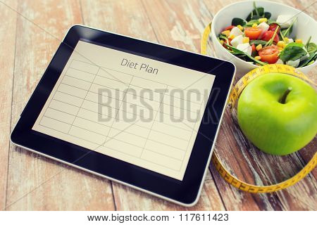 healthy eating, dieting and weigh loss concept - close up of diet plan on tablet pc screen, green apple, measuring tape and sald