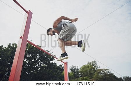 fitness, sport, exercising, training and lifestyle concept - young man jumping on horizontal bar outdoors