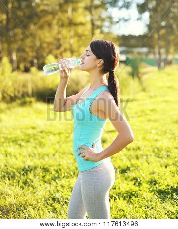 Sport And Fitness Concept - Beautiful Young Woman Drinking Water From Bottle