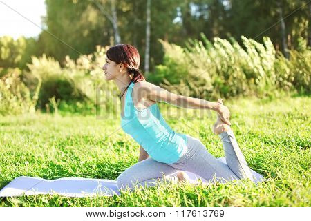 Woman Doing Yoga Exercises On Grass In Summer Day, Profile View