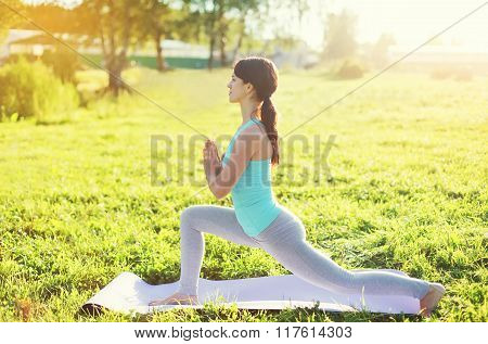 Yoga Woman Doing Stretching Exercises On Grass In Sunny Summer Day