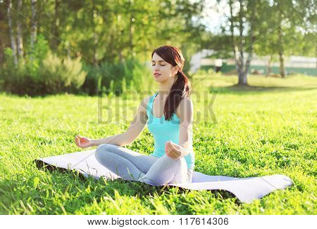 Yoga Woman Meditates On Grass Pose Lotus In Summer Day