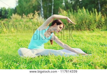 Young Woman Doing Yoga Exercises On Grass In Summer Day