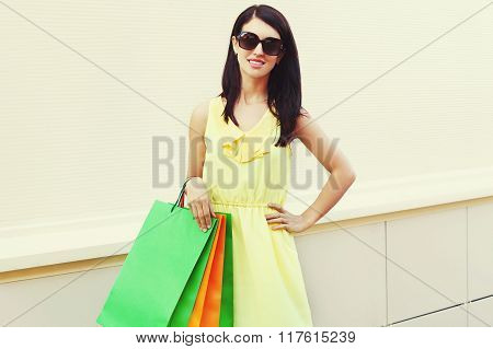 Beautiful Young Woman Wearing A Yellow Dress With Shopping Bags In City