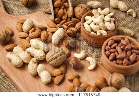 Almonds, Cashew, Walnuts And Hazelnuts In Wooden Bowls On Wooden And Burlap, Sack Background