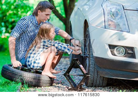 Adorable little girl sitting on a tire and helping father to change a car wheel outdoors on beautifu