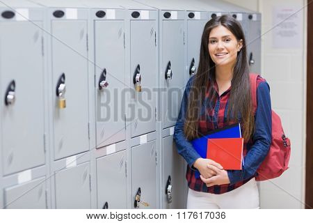 Smiling student posing near locker at university