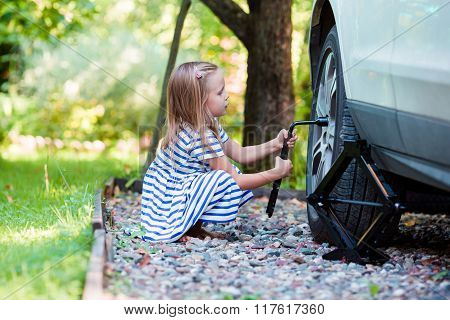 Adorable little girl changing a car wheel outdoors on beautiful summer day