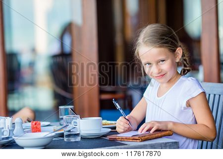Adorable little girl signs bill after having breakfast at outdoor cafe