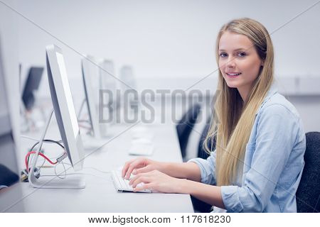 Smiling student working on computer at university