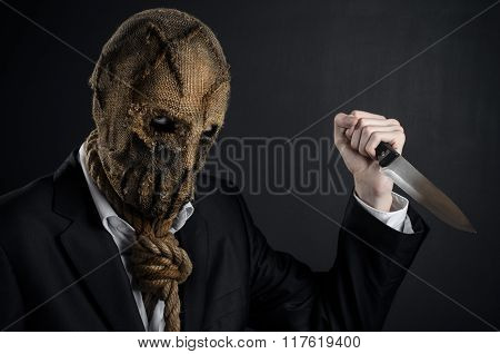 Fear And Halloween Theme: A Brutal Killer In A Mask Holding A Knife On A Dark Background In The Stud