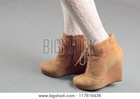 Beautiful Female Legs In Brown Suede Boots On A Gray Background