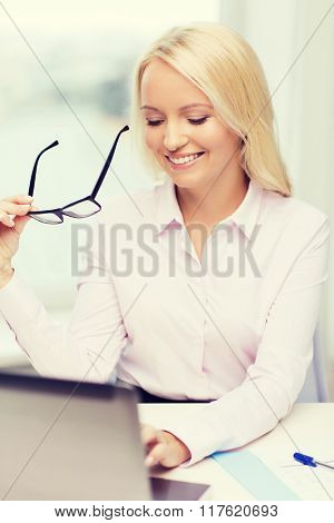 education, business and technology concept - smiling businesswoman or student with eyeglasses and laptop computer in office