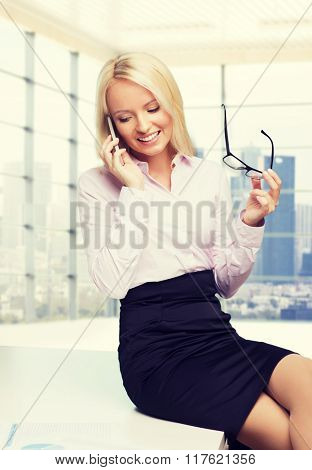 education, business, technology, communication and people concept - smiling businesswoman or secretary holding eyeglasses and calling on smartphone over office room with city view window background