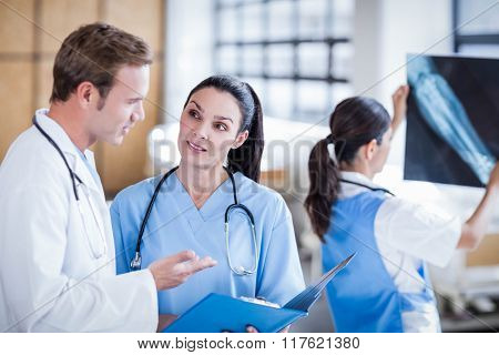 Medical team discussing the report on clipboard at hospital