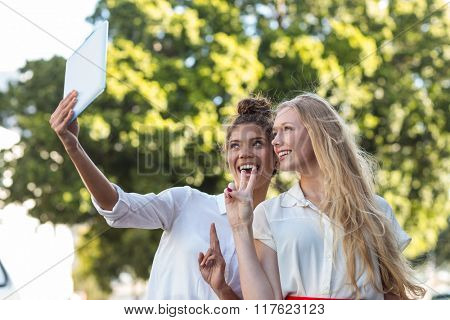 Hip friends taking selfies with tablet in the streets
