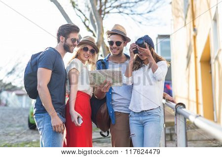 Hip friends taking pictures and checking map in the streets
