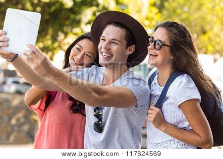 Hip friends looking at tablet in the streets