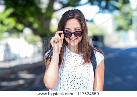 Hip girl holding her sunglasses in the streets