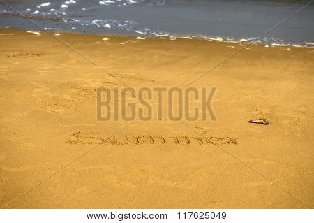 Inscription of summer on wet beach sand
