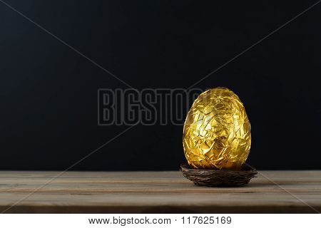 Easter Egg Wrapped In Gold Foil Paper With Black Background