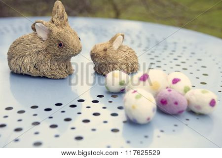 Straw Bunny With Easter Eggs On A Blue Table