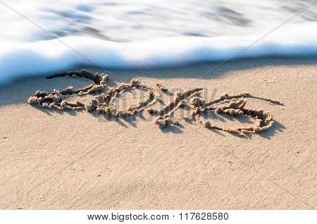 sign 2016 on a beach sand, the wave is almost covering digits. Summer travel concept