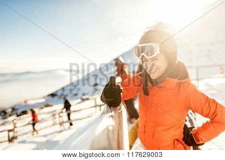 Woman Skier On Slopes. Portrait Of Young Woman Smiling In Skiing Equipment, Wearing Goggles And Helm
