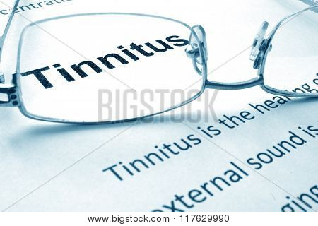 Paper with diagnosis Tinnitus and glasses.
