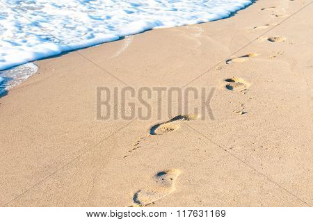 Footprints in the sand at sunset. Summer travel concept