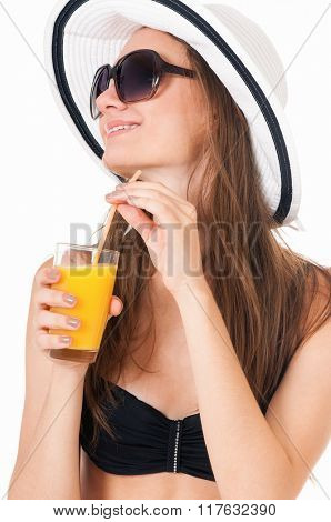 Pretty girl posing in bikini, summer hat and sunglasses, with orange juice, isolated on white background