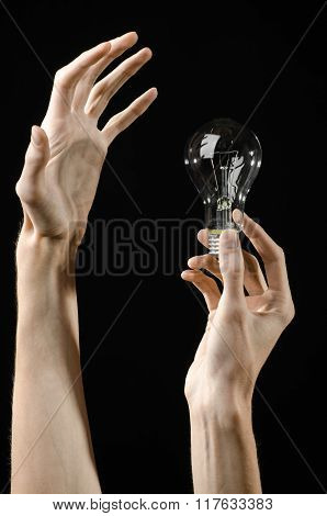Energy Consumption And Energy Saving Topic: Human Hand Holding A Light Bulb On Black Background In S