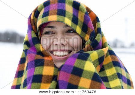The young woman has muffled in a multi-colored plaid and smiles