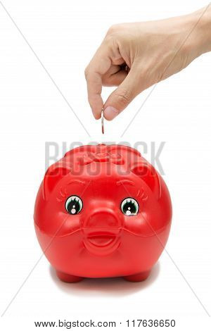 Hand Inserting Coin Into Piggybank Isolated On White Background