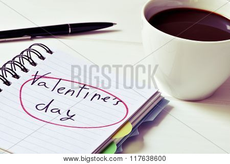 closeup of a notebook with the text valentines day handwritten in it, a pen and a cup of coffee on a white surface, with a filter effect
