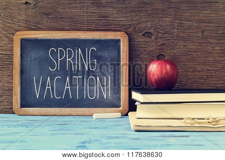 an old chalkboard with the text spring vacation written in it, a piece of chalk, and a red apple on a pile of books, on a blue rustic wooden table
