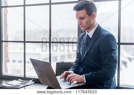 Businessman working on his laptop computer sitting in office