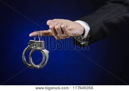 Corruption And Bribery Theme: Businessman In A Black Suit With Handcuffs On His Hands On A Dark Blue