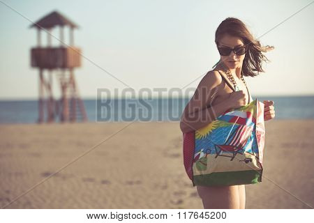 Attractive brunette woman with sunglasses carrying funny cartoon summer bag on the beach