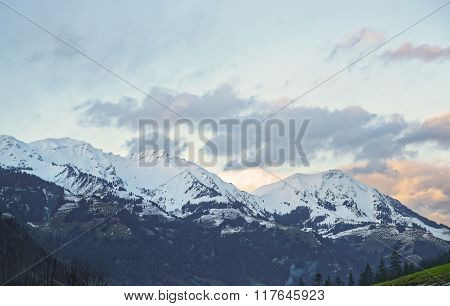 Road view to snow covered mountain in winter Switzerland. Switzerland is a country in Europe. Switzerland has a high mountain range from the Alps to Jura mountains.