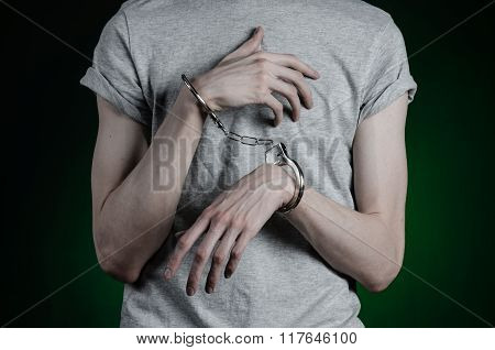 Prison And Convicted Topic: Man With Handcuffs On His Hands In A Gray T-shirt And Blue Jeans On A Da