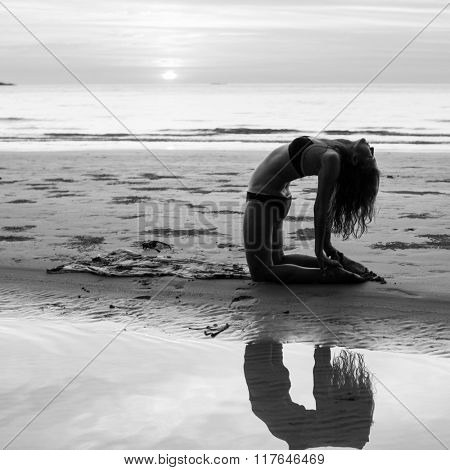 Woman silhouette yoga exercises on the beach during sunset. Black and white photography.