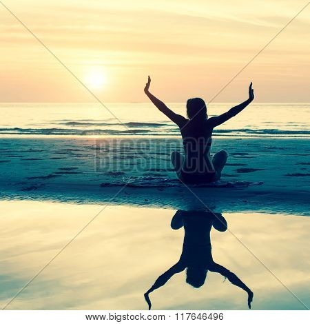 Young woman silhouette yoga exercises on the beach during sunset.