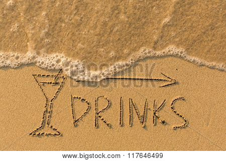 Word Drinks and arrow drawn on the sand of a beach with the soft wave.