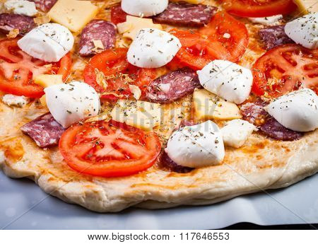 Raw pizza dough with mozzarella and proscuitto on top